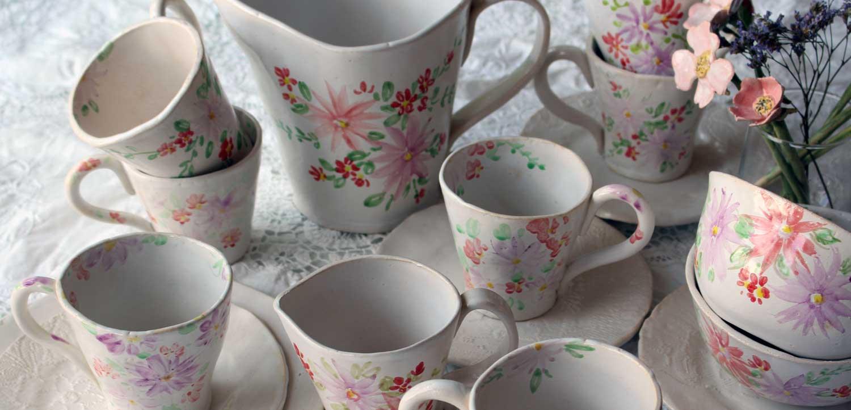 Nahaufnahme gedeckter Tisch mit bunten Blumen Keramikgeschirr
